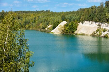 Deserted beach with clear turquoise water on old lake formed on site of chalk quarry in Grodno Belarus in summer sunny day with copy space under blue sky with clouds. 写真素材