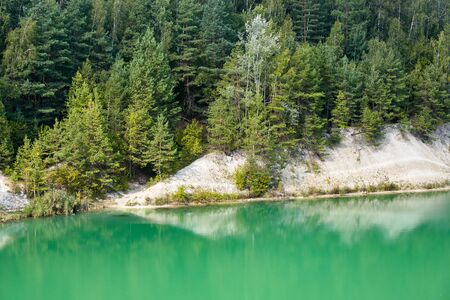 Deserted beach with clear turquoise water on old lake formed on site of chalk quarry in Grodno Belarus in summer sunny day with copy space 写真素材