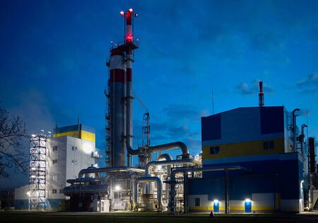 Beautiful scenic of petrochemical oil refinery plant shines with red and white lights at night.