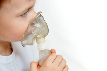 Child makes inhalation at home with nebulizer selective focuse on nebulaser mask with copy space. Example of combating respiratory diseases such as tracheitis bronchitis pneumonia.