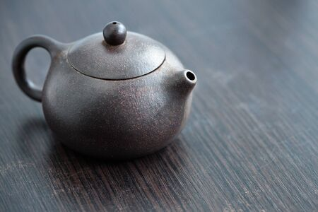 Old purple yixing clay Chinese teapot yuan zhu hu type for tea ceremony or gong fu cha or kung fu tea for brewing oolong, red green white yello shou shu and sheng puerh cha on wooden table or chaban