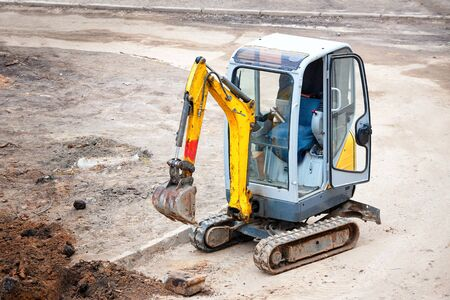 Tracked mini excavator breaks out old curbs before installing new curbs. The concept of using economical and compact equipment for urban needs. Imagens