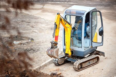 Tracked mini excavator breaks out old curbs before installing new curbs. The concept of using economical and compact equipment for urban needs.