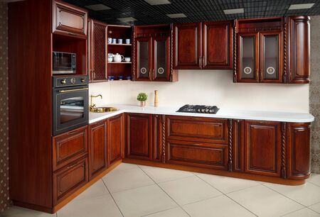Interior of modern kitchen in classic style with golden elements cherry alder wood cabinetry with built-in appliances electric or induction hob, electric oven stone sink and extractor fan.