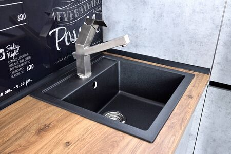 Modern design chrome water tap over black stone kitchen sink on table top made of wood with chalk lettering background Stock Photo - 144722737