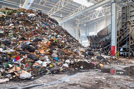 Solving problem of environmental pollution with waste at garbage processing plant - huge pile of garbage prepared for loading to conveyor belt for further sorting and processing, with copyspase.
