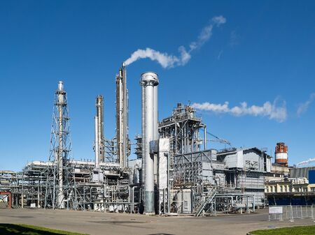 Exterior of a modern silver petrochemical installation with reactors converters furnace chimneys communications over blue sky background with copyspace.