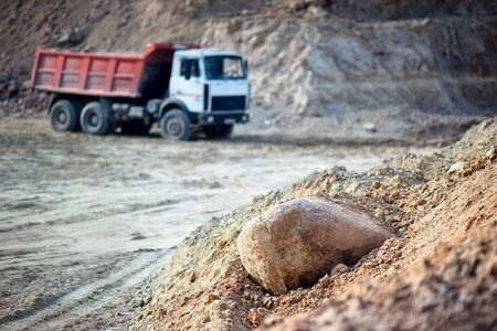 Pile of ore rocks over out of focus background with heavy multi-ton heavy mining truck exporting minerals from open-pit mine. Concept of shipping, and protecting the environment and nature. Stok Fotoğraf