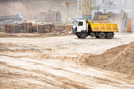 Multi-ton heavy mining dump truck loaded during removal of construction soil from construction site. Concept of providing transport shipping and freight for major construction projects, with copyspace Imagens