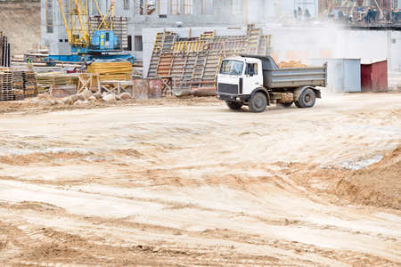 Multi-ton dump heavy mining truck loaded during removal of construction soil from construction site. Concept of providing transport shipping and freight for major construction projects, with copyspace