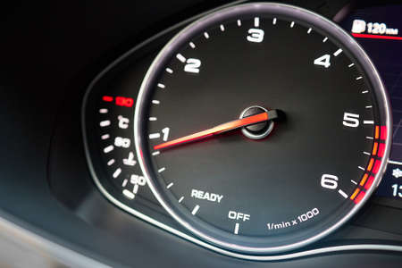 Rev counter of car selective focus closeup with copyspace.Tachometer or revolution counter, RPM gauge with red glowing needle on car dashboard with fuel and engine temperature indicators.