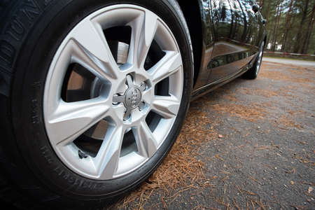GRODNO, BELARUS - DECEMBER 2019: Audi A6 4G C7 Luxury car closeup alloy wheel with Dunlop winter tires side view with titanium look matt finish with fall forest background.