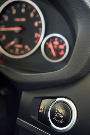 Selective focus on red enlightened Car Start Stop Engine Button. Element of interior inside car, vertical with copy space. Reklamní fotografie