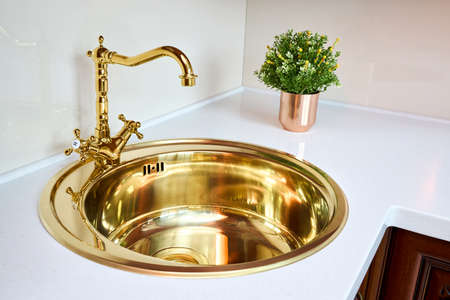 Kitchen luxurious interior with golden brass sink and faucet double tap mixer in contemporary modern design with stone marble stoneware countertop cherry hardwood panels and flower pot.