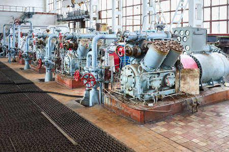 Interior element of chemical enterprise. Row of ammonia reciprocating compressors with cylinders and electric motor with control panel, with control devices and alarm systems. Archivio Fotografico