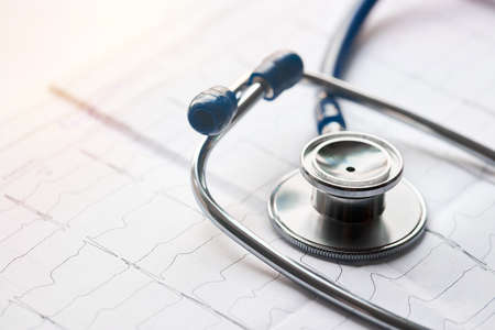 Medical concept. Cardiogram with stethoscope selective focus closeup background with copyspace and sunflare.