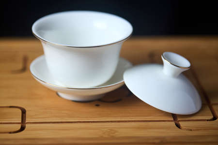 Gaiwan on chaban selective focus. Tea ceremony gong fu cha. Chinese white pottery Dehua white Chinese porcelain gaiwan bowl tea cup and lid with gold border on bamboo teaboard tea tray or chaban. Standard-Bild