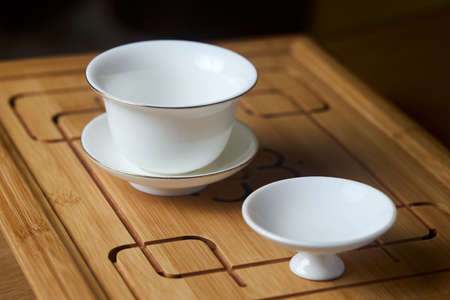 Gaiwan on chaban selective focus. Tea ceremony gong fu cha. Chinese white pottery Dehua white Chinese porcelain gaiwan bowl tea cup and lid plate with gold border on bamboo teaboard tea tray chaban