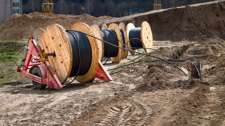 Cable high voltage electric in roll or round coil on ground. Concept of electricity supply for construction projects. Several wooden coils with power cable laid in trench 16x9 image.