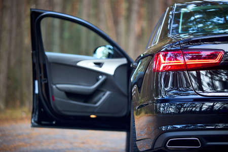 GRODNO, BELARUS - DECEMBER 2019: Audi A6 4G, C7 2016 Left back rearlight of black metallic car shot closeup with opened door out of focus on forest background with copyspace.