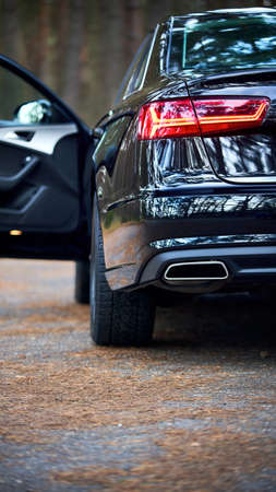 GRODNO, BELARUS - DECEMBER 2019: Audi A6 4G, C7 2016 Left back rearlight of black metallic car shot closeup with opened door out of focus on forest background with copyspace 16x9.