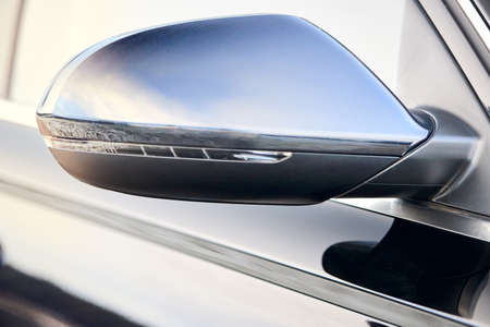 Luxury Black car parts right side driver car exterior mirror with turn signal repeater closeup selective focus with sky and clouds reflection, copyspace.