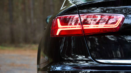 GRODNO, BELARUS - DECEMBER 2019: Audi A6 4G, C7 2016 Left back led modern rear light or taillight of black metallic car shot closeup selective focus on out of focus forest background with copyspace.
