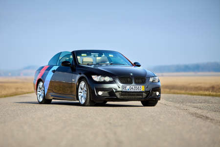 Berlin - April 2014: : BMW 3 series E93 328i convertible with m-pack logo stripes outdoors. Open roof cabrio. BMW cabriolet 3-series in field country road under spring blue sky with copyspace. Editorial