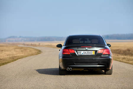 Berlin - April 2014: : BMW 3 series E93 328i convertible with m-pack logo stripes outdoors. Rear back view. BMW cabriolet 3-series in field country road under spring blue sky with copyspace.