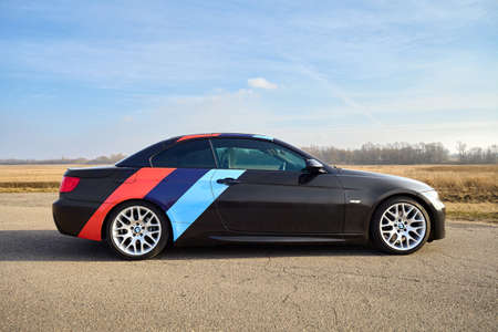 Berlin - April 2014: : BMW 3 series E93 328i convertible with m-pack logo stripes outdoors. Right side view. BMW cabriolet 3-series in field country road under spring blue sky with copyspace.