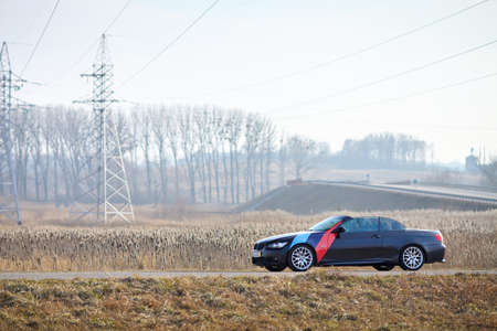 Berlin - April 2014: : BMW 3 series E93 328i convertible with m-pack logo stripes outdoors. Left side view. BMW cabriolet 3-series in field country road with high voltage masts wires with copyspace. Editorial