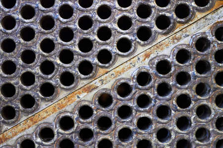 Tube sheet plate of heat exchanger or boiler closeup texture macro diagonal background with insoluble hard mineral deposits salts scale welding seams and corrosion. Trypophobia concept. Standard-Bild
