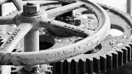 Old grunge steampunk valve wheel with gear gearbox selective focus with handle grip over out of focus industrial metal BW background 16x9 with copyspace in black and white.