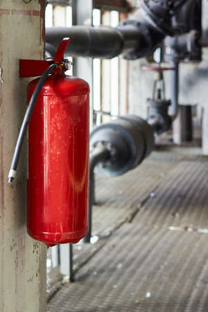 Fire extinguisher security guard equipment in factory for fire protection system. Carbon dioxide fire extinguisher with pressure gauge in industrial room vertical. Fire safety protection concept.