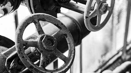 Two old grunge steampunk valve wheels selective focus with handle grip over out of focus industrial metal BW background 16x9 with copyspace in black and white.
