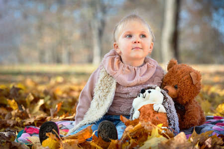 Little beautiful dreamy caucasian girl with earrings in autumn park sits in golden autumn leaves with with soft toys hedgehog and bear cub over fall background with copyspace.