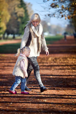 Happy caucasian mother and her little daughter walk together in park holding hands together in warm sunny autumn day, vertical shot.