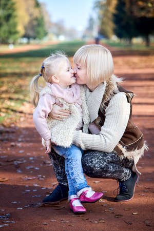 Scene of quiet family happiness and love. Happy caucasian mother holding her little daughter on her laps face to face closely in park together in warm sunny autumn day, vertical shot.