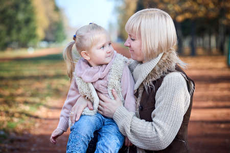 Scene of quiet family happiness filiation and love. Happy caucasian mother holding her little daughter on her laps face to face closely looking into each others eyes in park in warm sunny autumn day.