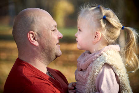 Scene of quiet family happiness filiation and love. Happy caucasian father and his little daughter face to face closely looking into each others eyes in sunny autumn park among fallen golden leaves.