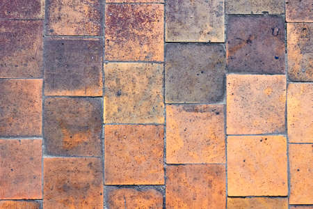 Orange brown purple old shabby worn out floor tiles with damages cracks dirt caverns potholes and paint stains. Art design background texture.