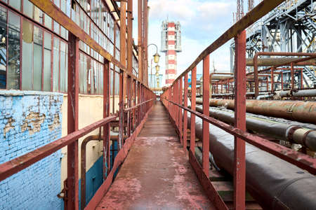 Industry highway walkway platform with grate and handrail on petrochemical plant factory with lighting masts and explosion-proof fireproof design rusty retro style lanterns and urea tower granulator. Standard-Bild