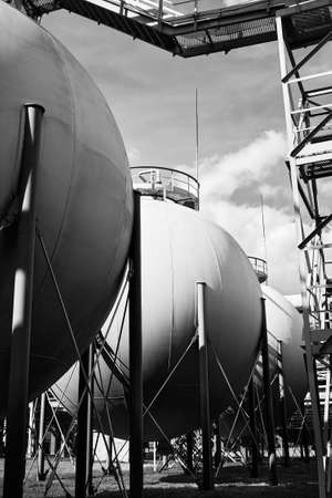 Industrial landscape bottom up view on several spherical gasholders tanks with lightning protection and safety valve on modern chemical production. Black and white industrial petrochemical background.