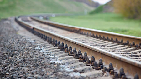Selective focus railway track turns and twists between out of focus hills background. Empty rounding and turning single track of railways. Shallow focus perspective of rounded rails bend horizontal. Standard-Bild