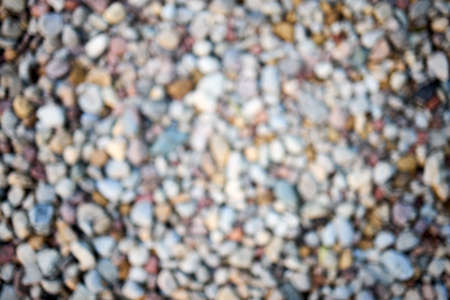 Calm river beach shore stone abstract blur. Defocused abstract background of multicolored pebbles or pebble stones on the shore closeup. Blurred defocused abstract background.