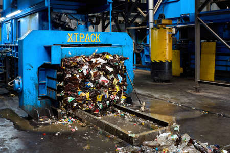 Grodno, Belarus - October 2018: XTPack medium sized full automatic baler at work for compressing waste OCC, plastic film, HDPE, PET, steel cans, aluminum cans and hard plastic for its further reuse.