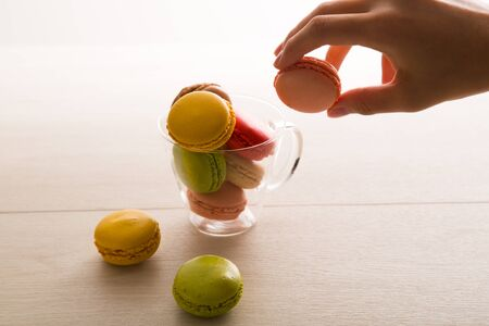 pinching: Macaron and womens hands