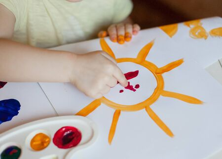 only baby girls: Little girl draws paints the sun,close-up only hands and figure