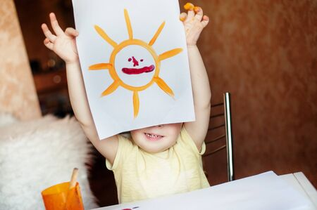 color image creativity: A little girl shows a picture of sun and smiles