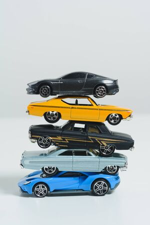 Stack of toy cars, conceptual, vertical.